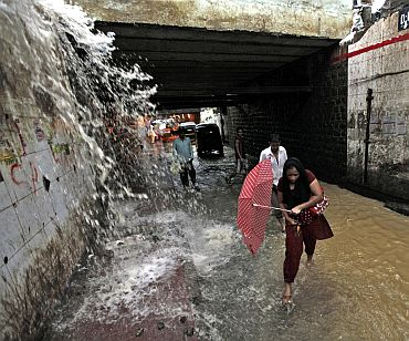 People wade through a flooded underpass road during monsoon rains in Mumbai