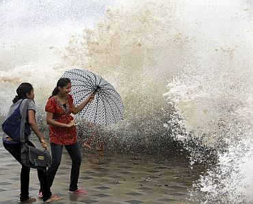 Women use an umbrella to protect themselves during high tide at Mumbai's seafront