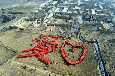 Villagers hold pieces of red cloth to form the Chinese character 'love' to welcome the Lantern Festival on the outskirts of Taiyuan, Shanxi province, China