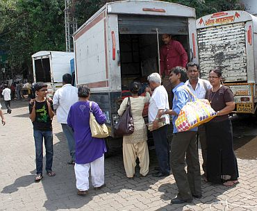 People hitch a ride in a goods carrier