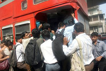 People jostle to enter a crowded public transport bus