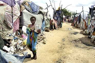A displaced Somali girl carries dishes as she walks past her makeshift shelter in Jabuti refugee camp in south Mogadishu June 20, 2010