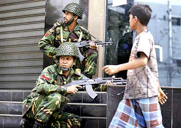 A boy walks past soldiers outside the headquarters of the paramilitary Bangladesh Rifles in Dhaka