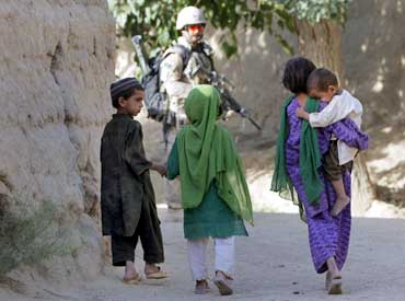 Children walk as a Canadian soldier patrols in Nakhonay village in Afghanistan in June 2010