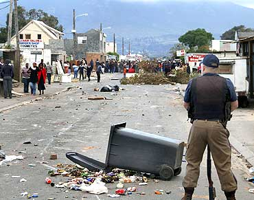 A police officer stands guard as protesting residents unhappy with living conditions look on at Masiphumelele informal settlement in Cape Town, on July 30, 2009