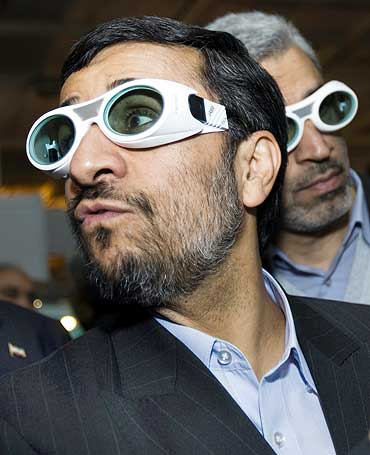 Iran's President Mahmoud Ahmadinejad wears protective glasses while visiting an exhibition of laser science and technology in Tehran