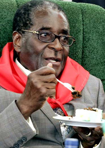Zimbabwe's President Robert Mugabe eats cake during celebrations for his 85th birthday
