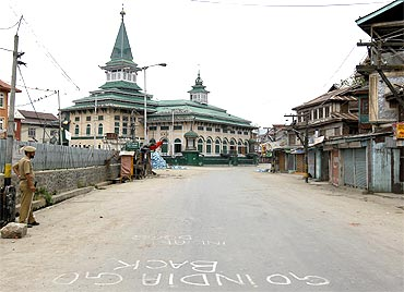A policeman stands guard along a deserted road in Srinagar
