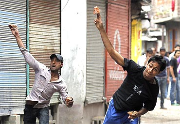 Kashmiri protesters throw stones towards the police during a protest in Srinagar