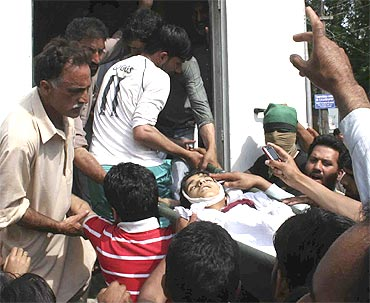People carry nine-year-old Tariq Ahmad in Baramulla