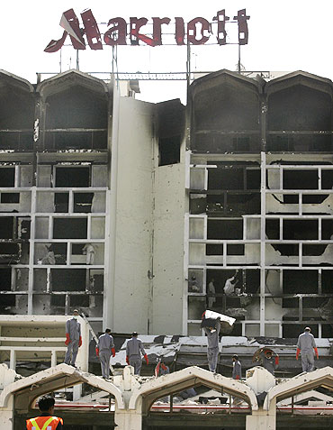 Workers remove debris at the destroyed Marriott hotel in Islamabad