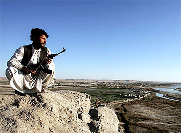 An Afghan policeman patrols mountains surrounding Helmand river valley in southern Afghanistan