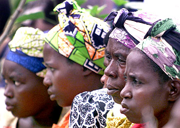 Rwandan women listen to proceedings at the first session of a new court system aimed at letting ordinary people judge those accused of killing their families and friends during the 1994 genocide