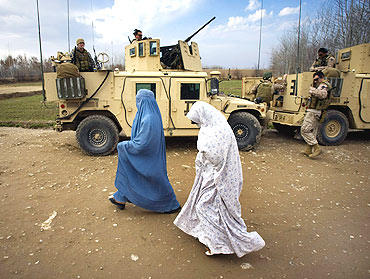 Afghan women walk past a US military vehicle of NATO's International Security Assistance Force in Siavashan village near Herat