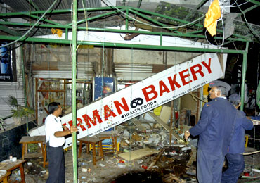 Firefighters examine the German Bakery blast site in Pune