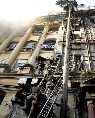 Rescuers and firemen try to evacuate people after a fire broke out in a building in Park Street, Kol