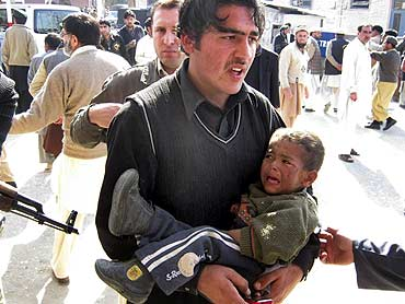 A man carries an injured boy from the site of a bombing at Timergara, Lower Dir, Pakistan