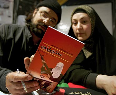 Mohammad (Left) and Ganan Najarhai read a booklet about women suicide bombers as they sign up to volunteer as suicide bombers in support of the Palestinian people during an exhibition about Hamas in Tehran