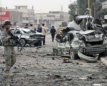 A US soldier stands guard near the wreckage of vehicles after a bomb attack in northern Baghdad