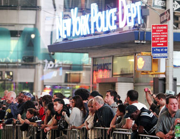 People hang around Times Square as police and fire personnel cordon off  the area