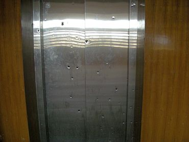 A bullet-ridden lift door at the hospital