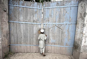 A boy looks through the main gate of the ancestral home of the family of Faisal Shahzad in Pakistan'
