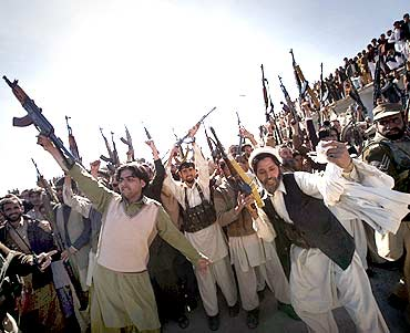 Members of the local Lashka hold their weapons while dancing in a show-of-force in Khar, Pakistan
