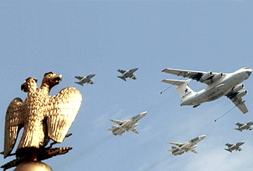 Russian fighters and a flight refuelling tanker fly in formation over the two-headed eagle