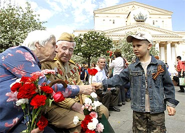 Russian World War Two veterans receive a flower from a boy in front of the Bolshoi Theatre