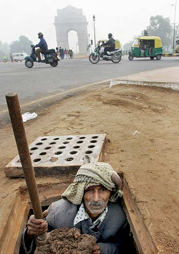 A sweeper cleans a gutter near India Gate in New Delhi