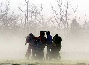 Villagers cover themselves from a sandstorm near India-Nepal border in Pilibhit in Uttar Pradesh