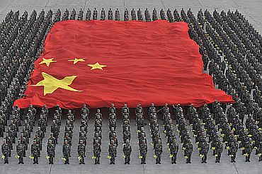 Paramilitary policemen hold a Chinese national flag during a parade training session in Beijing
