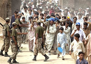 Soldiers try to control a mob of internally displaced men at a camp in Swat