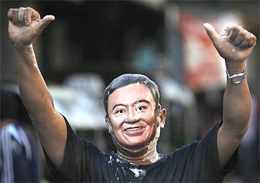 A Red Shirt supporter wears a Thaksin Shinawatra mask during protests in Bangkok