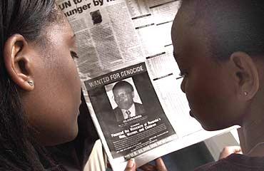 Readers look at a newspaper carrying the photograph of Felicien Kabuga
