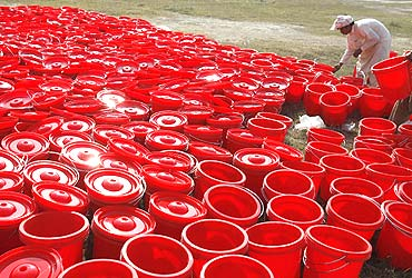 A worker sorts out water-pots at a camp for internally displaced people fleeing the offensive in South Waziristan