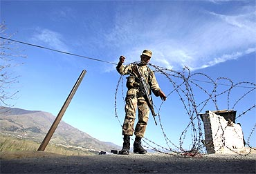 A soldier creates a barrier at a security checkpoint in Swat valley