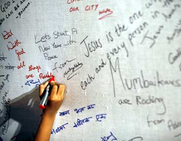 A girl writes a message dedicated to the victims of the Mumbai terror attacks