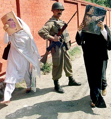 College girls hide their faces with their text books while a trooper keeps guard in Srinagar
