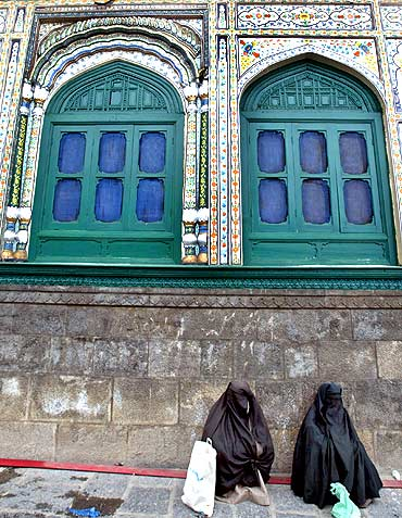 Women beggars wait at a Sufi shrine