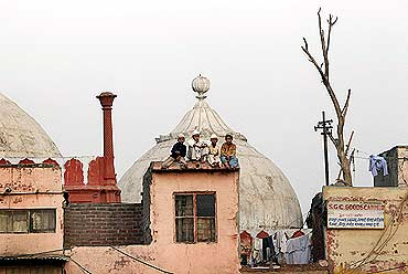 Muslim children sit on the roof of a house next to a mosque