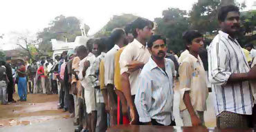 People stand in queue to collect relief materials