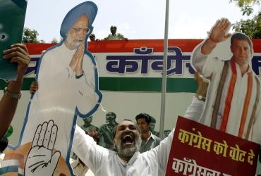 A man holds cut-out images of Dr Singh and Rahul Gandhi