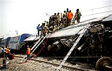 Army troopers and rescue workers conduct rescue operations at the site of the train accident