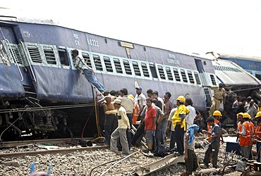 Rescue workers gather near the wreckage of the train