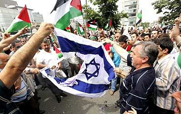 Demonstrators try to set afire Israeli flag during a protest near the Israeli Consulate in Istanbul