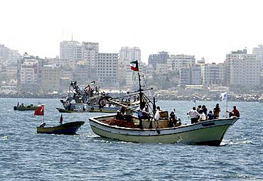 Palestinians ride aboard boats in a preparation for the arrival of a convoy of ships to Gaza's port