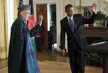 Obama and Afghan President Karzai wave after a joint news conference in White House