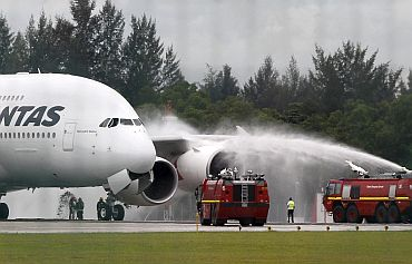 The Qantas Airways 380 passenger plane flight QF32 is sprayed by rescue services