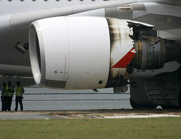 Airport ground crew stands near the partially damaged engine